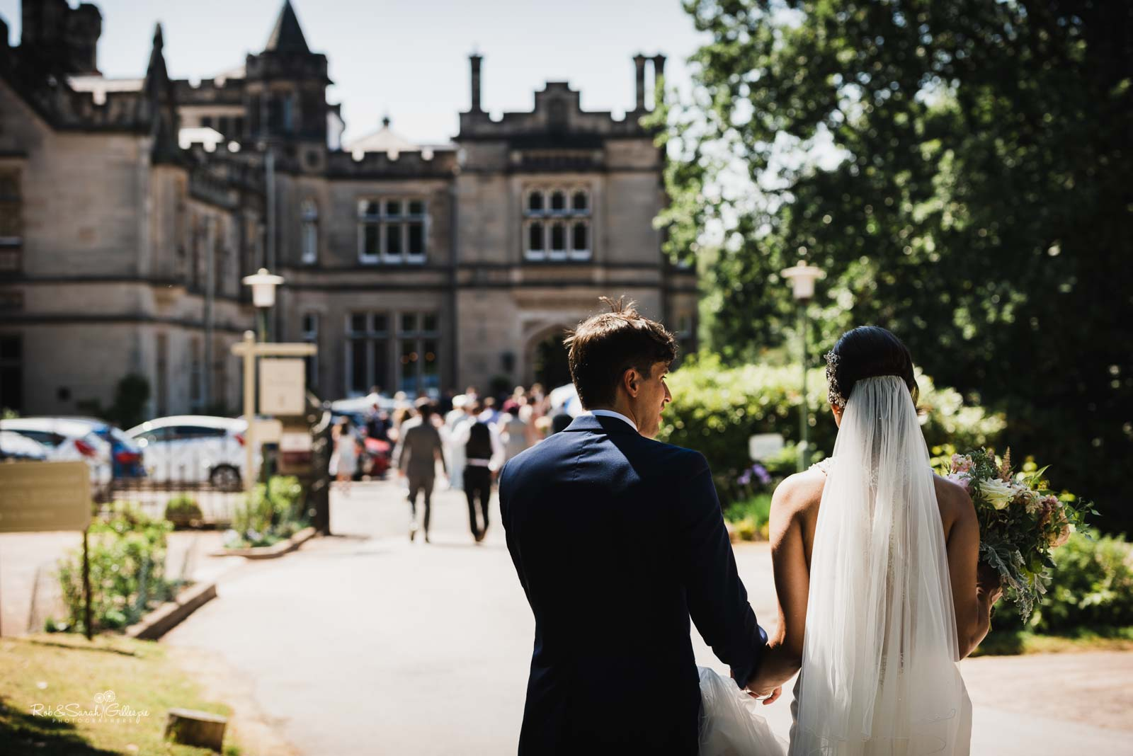 Bride and groom walk to Hampton Manor for wedding reception