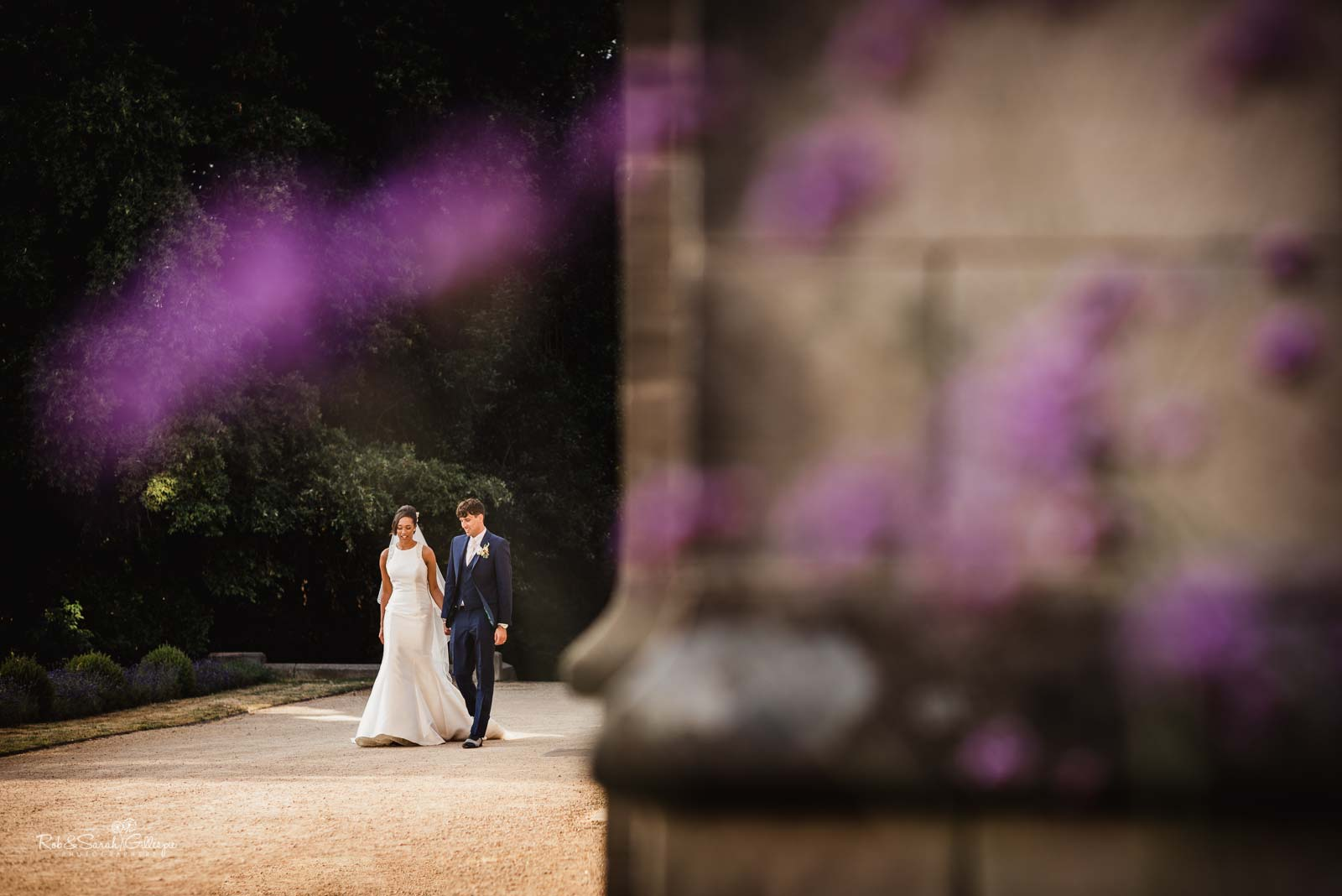 Bride and groom walking through grounds at Hampton Manor