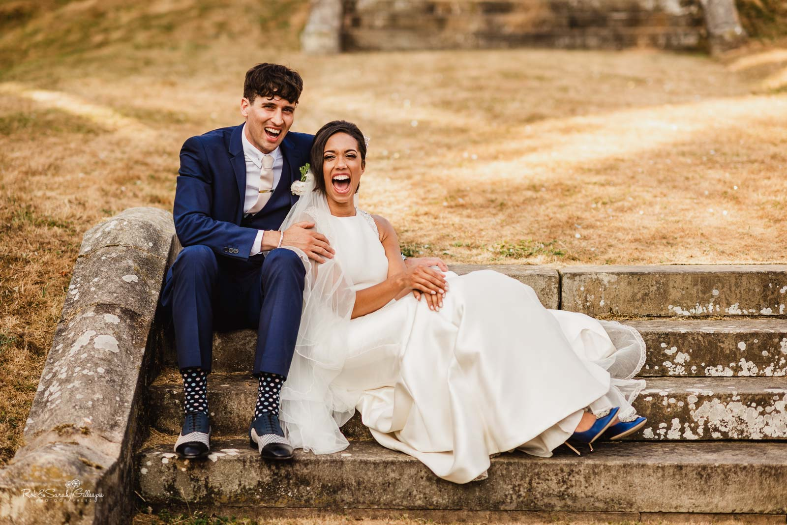 Bride and groom laughing sitting on steps at Hampton Manor