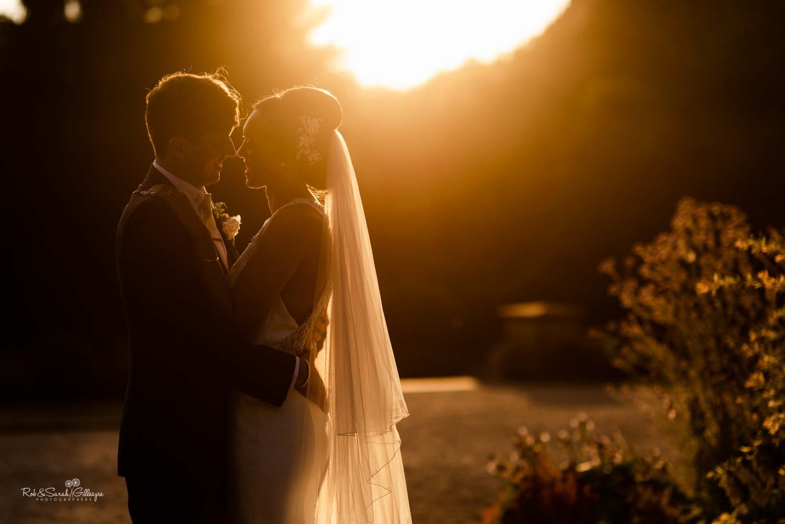 Bride and groom at Hampton Manor, backlit with evening sunlight