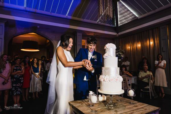 Bride and groom cut wedding caker at Hampton Manor