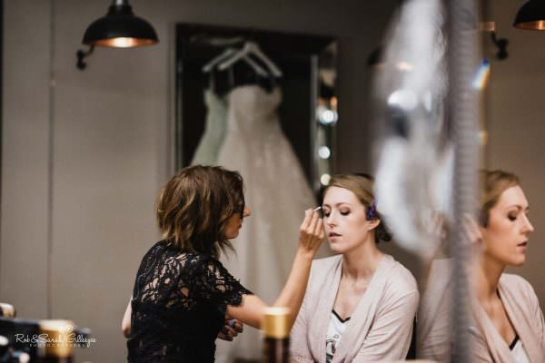 Bride has makeup applied at The Mill Barns