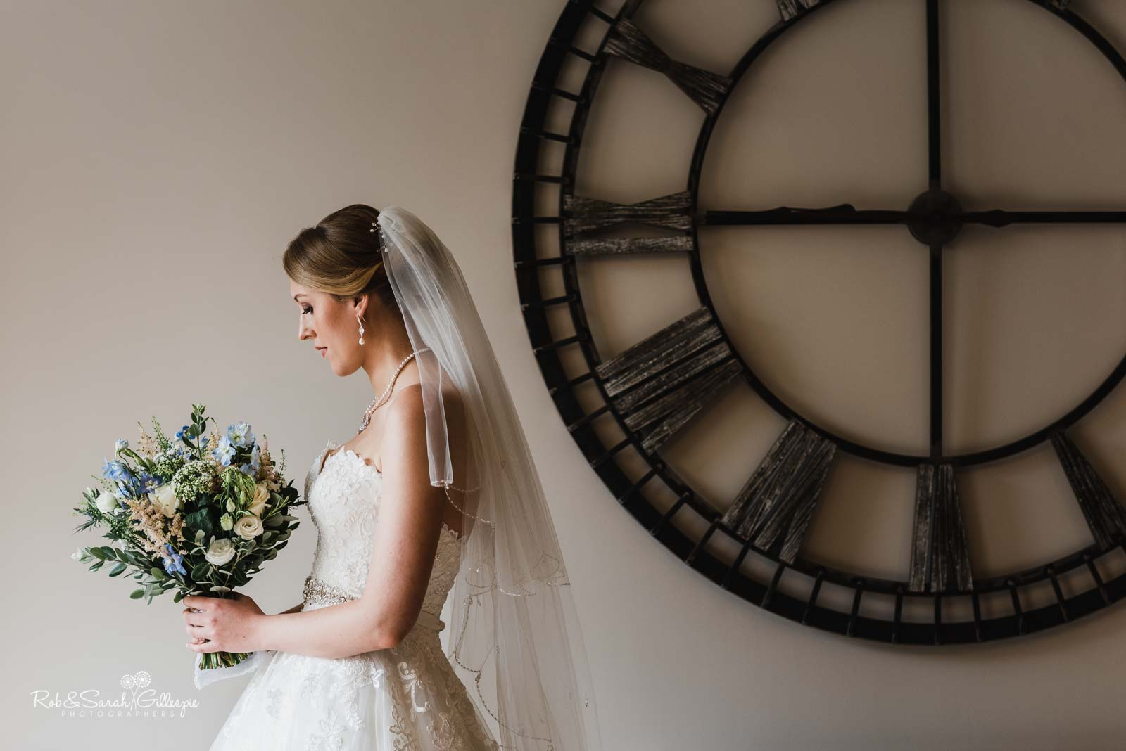 Beautiful portrait of bride at The Mill Barns with large clock on wall
