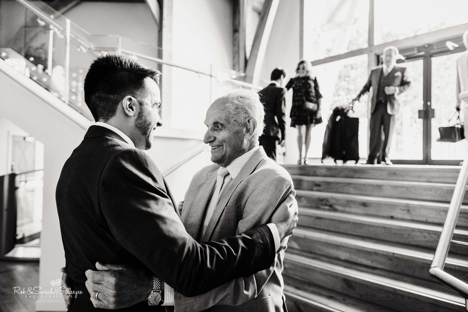 Groom hugs grandfather at The Mill Barns wedding