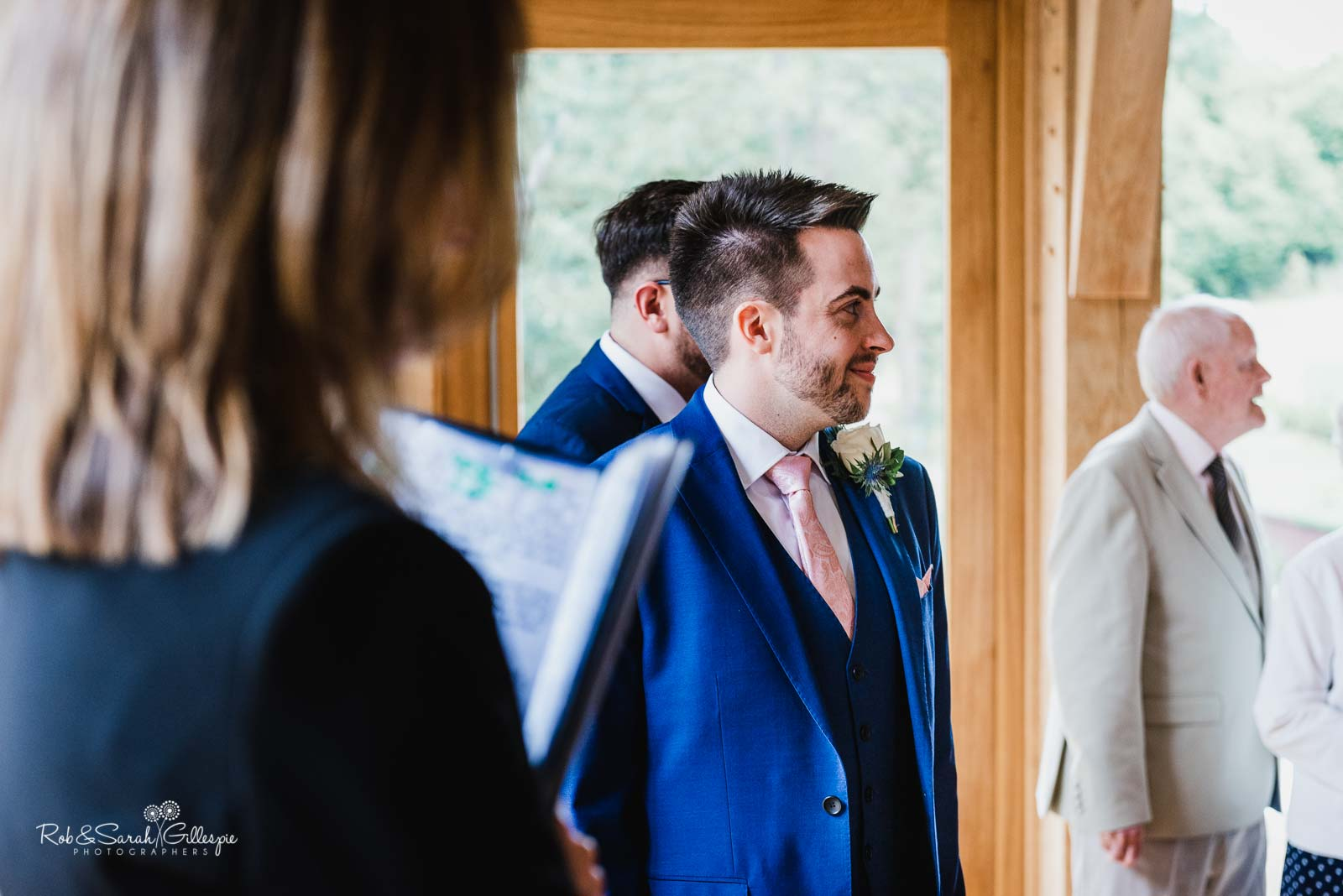 Groom smiling as bride arrives at The Mill Barns wedding ceremony