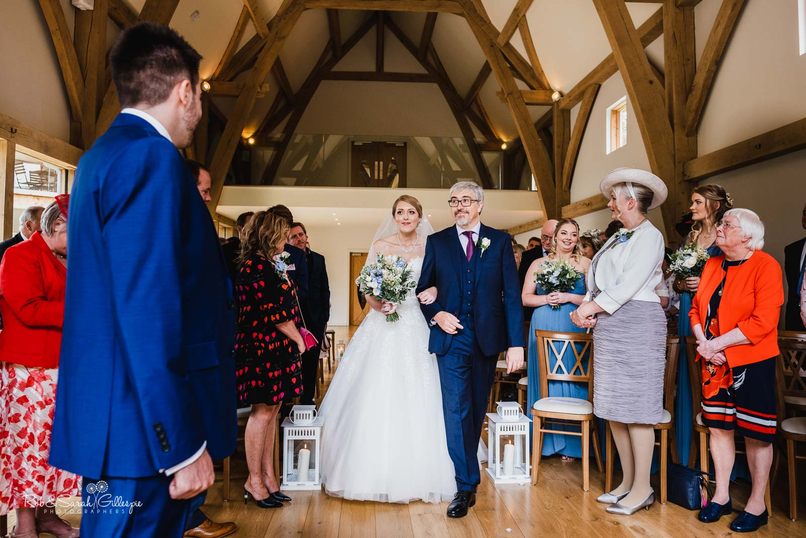 Bride and father walk up the aisle at The Mill Barns