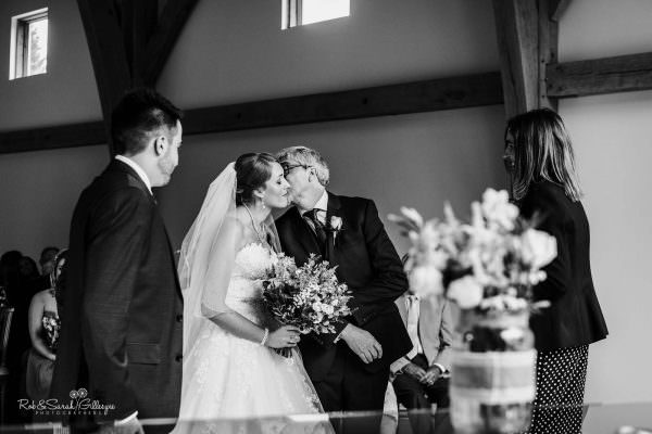 Dad kisses daughter during wedding ceremony at The Mill Barns
