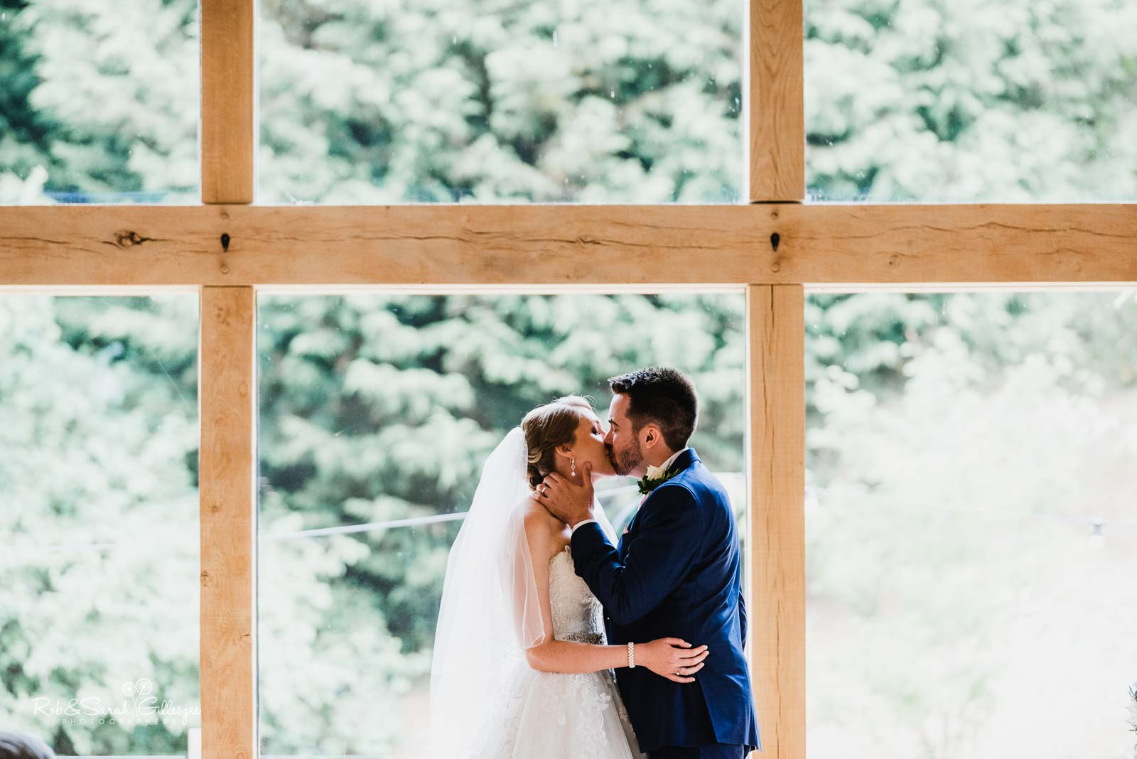 Bride and groom kiss during wedding ceremony at The Mill Barns