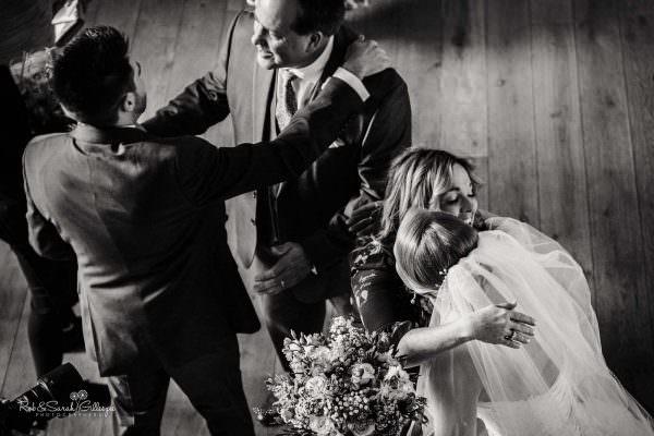Wedding guests at The Mill Barns hug bride and groom
