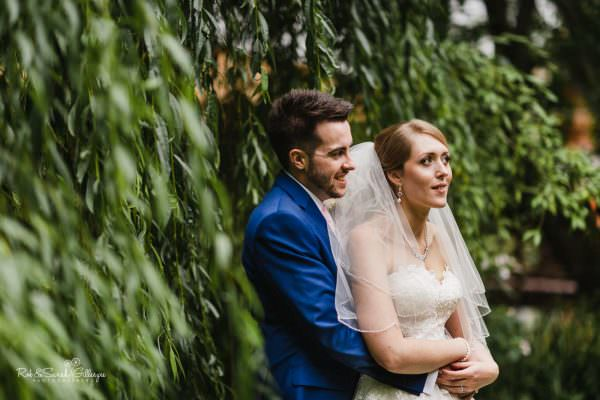 Bride and groom together at The Mill Barns in beautiful light surrounded by trees