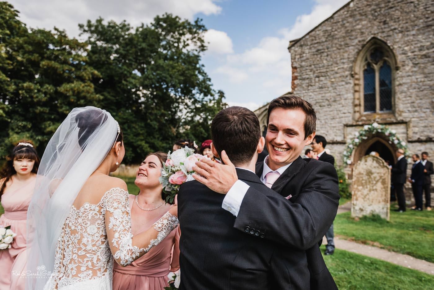 Wedding guests congratulate bride and groom at Bourton-on-Dunsmore church