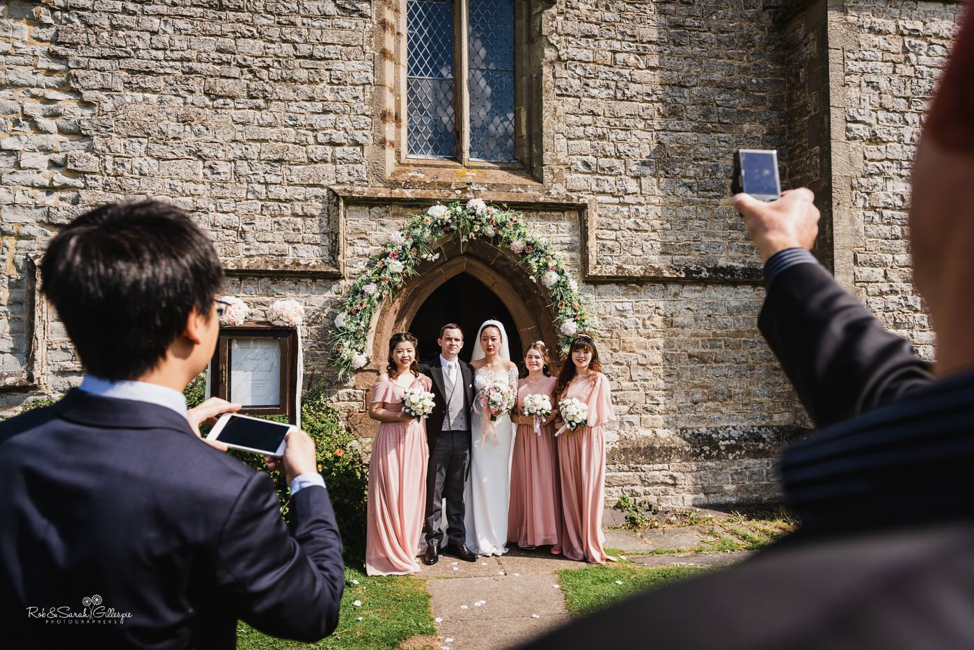 Bridal party pose for guest photos at Bourton-on-Dunsmore church