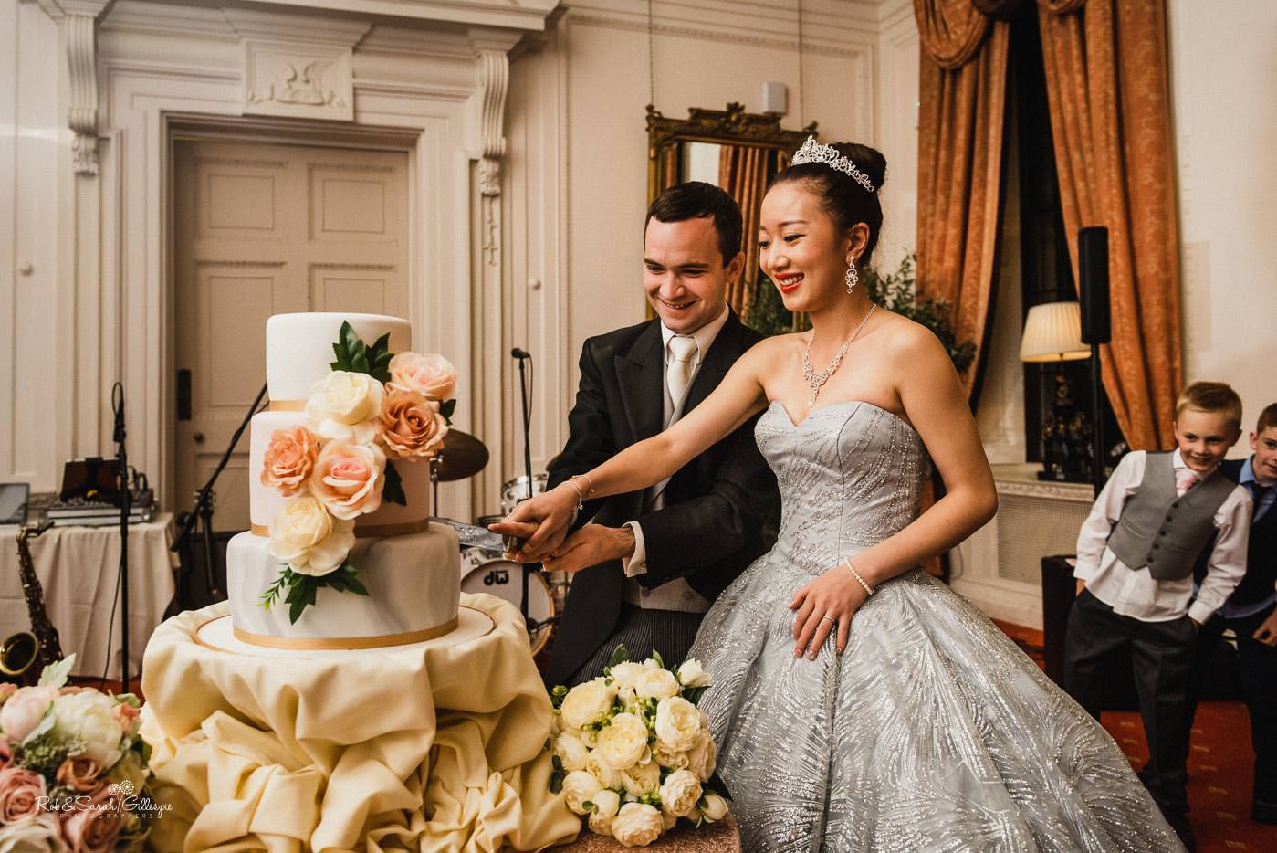 Bride and groom cut wedding cake at Coombe Abbey
