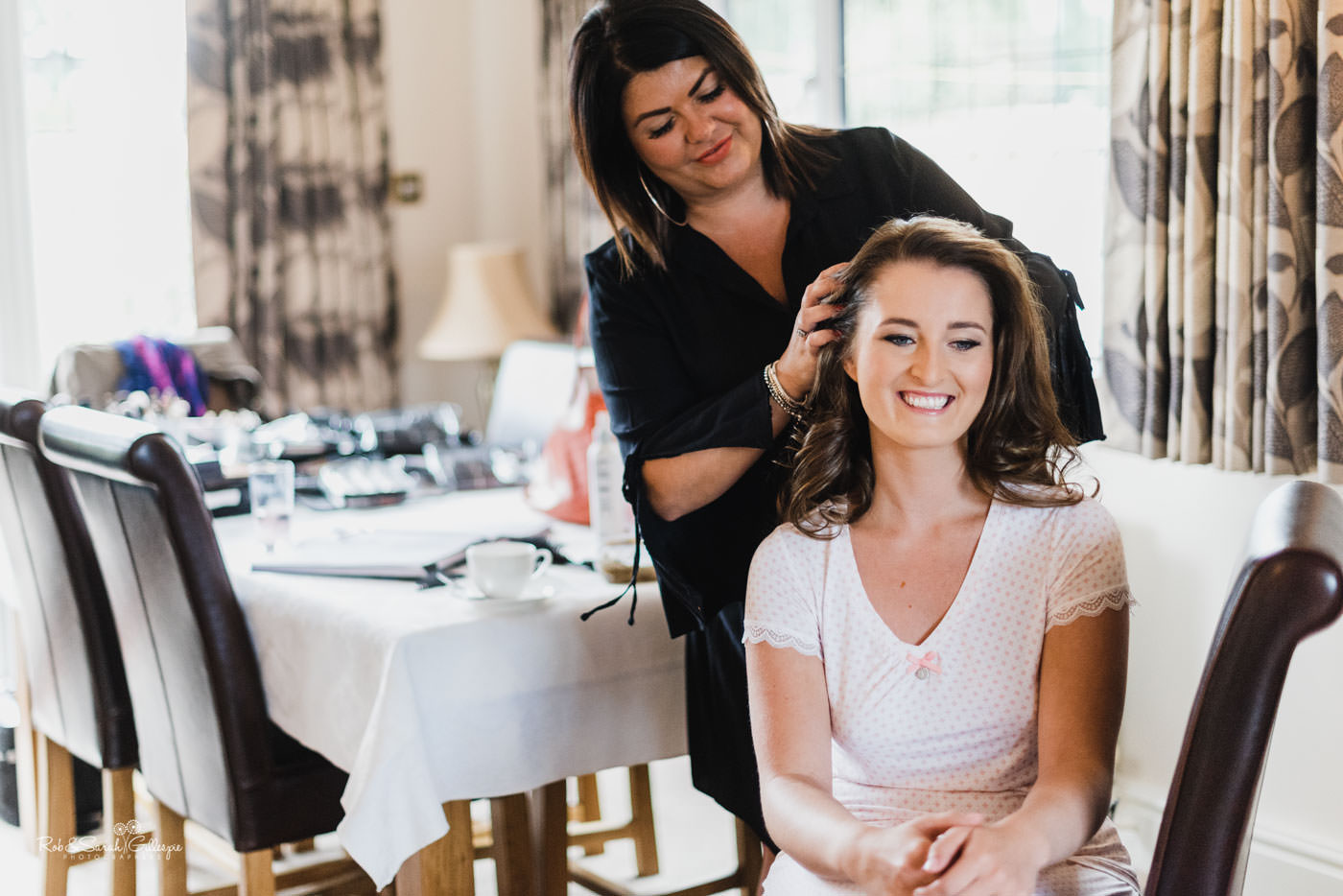 Bride smiling as her hair is styled for wedding
