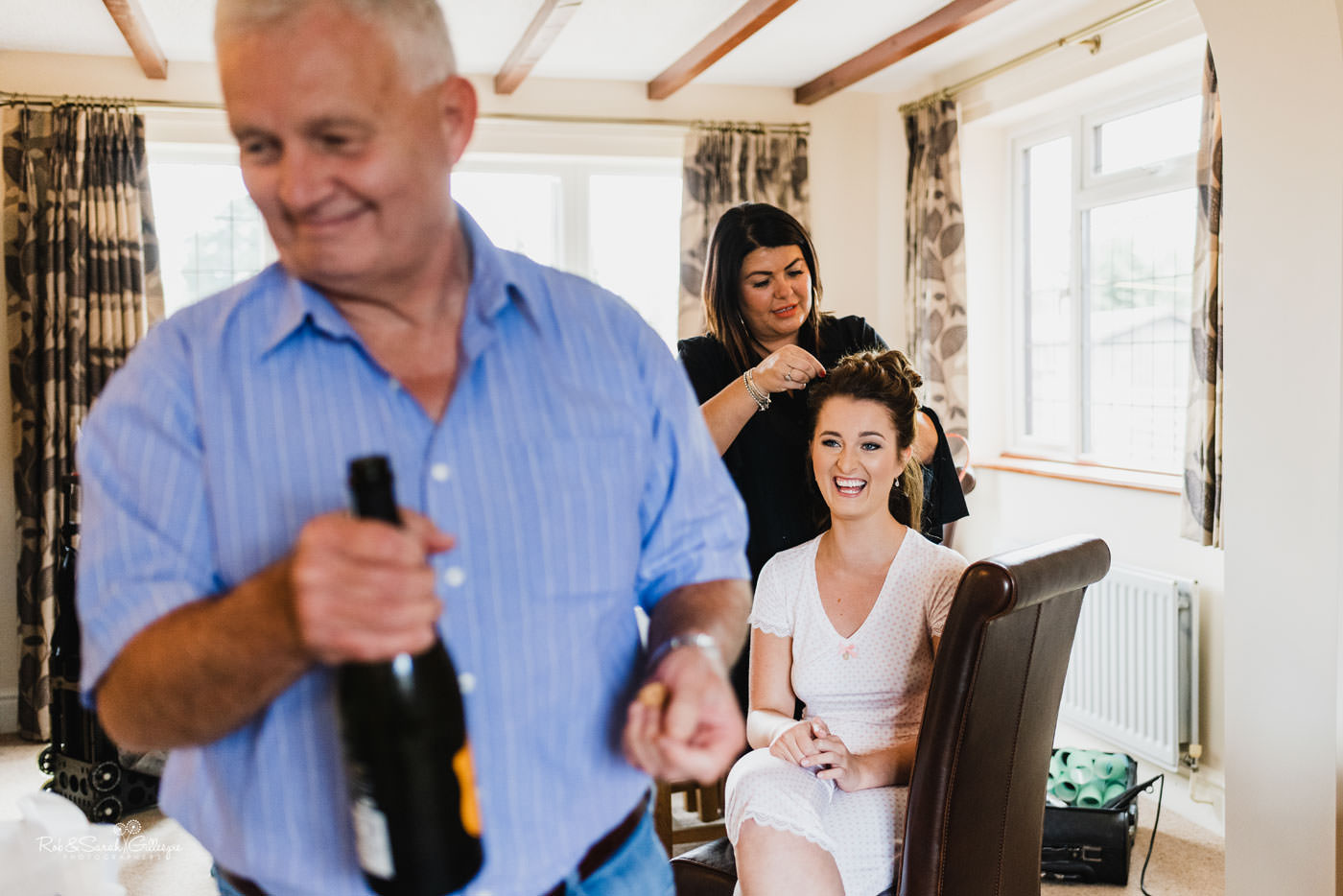 Bride laughing as dad opens champagne on wedding day