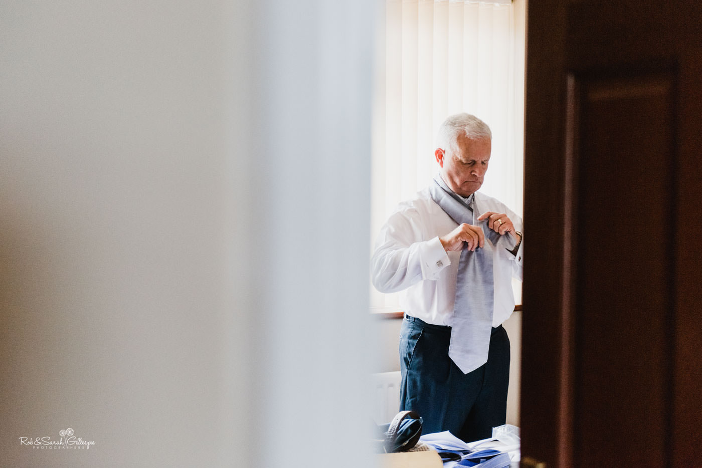 Bride's dad fixes tie as he prepares for wedding