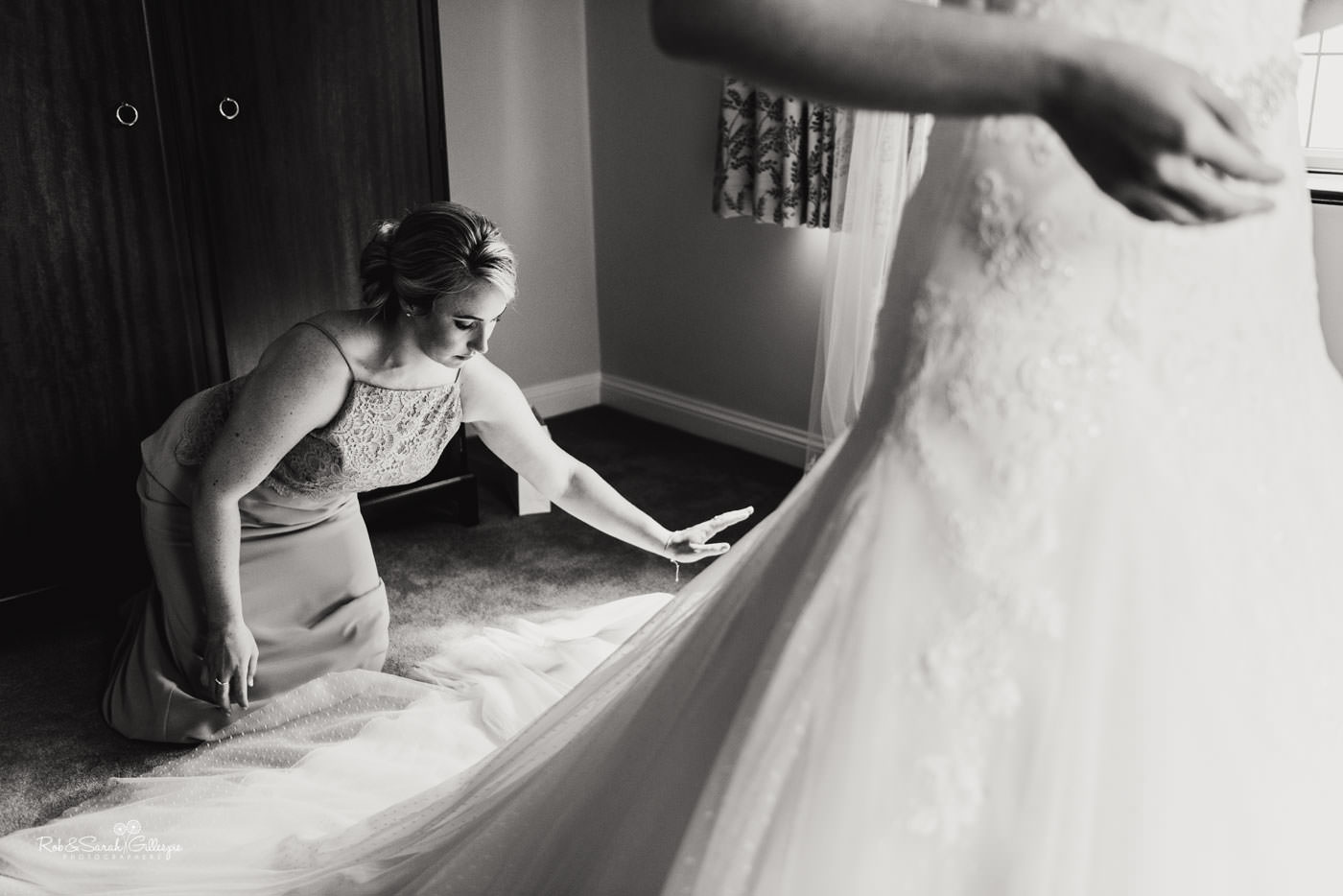 Bridesmaids helps bride into her wedding dress