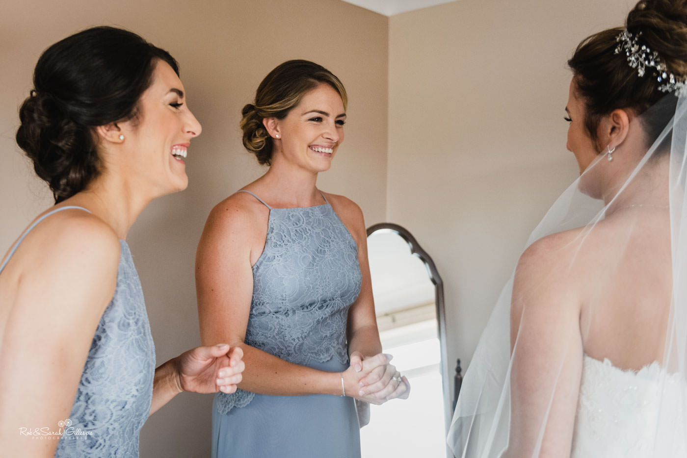 Bridesmaids laughing with bride as she gets ready for wedding