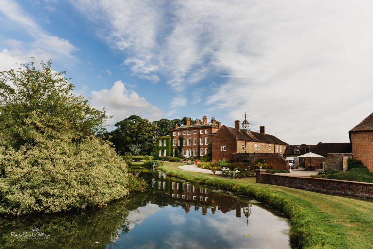 View of Delbury Hall wedding venue with lake, trees and surrounding buildings