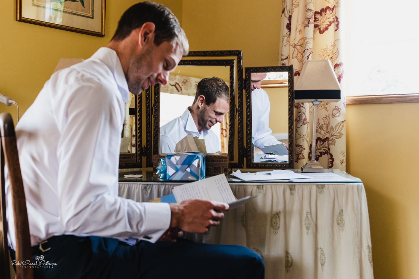 Groom reads card from bride before Delbury Hall wedding