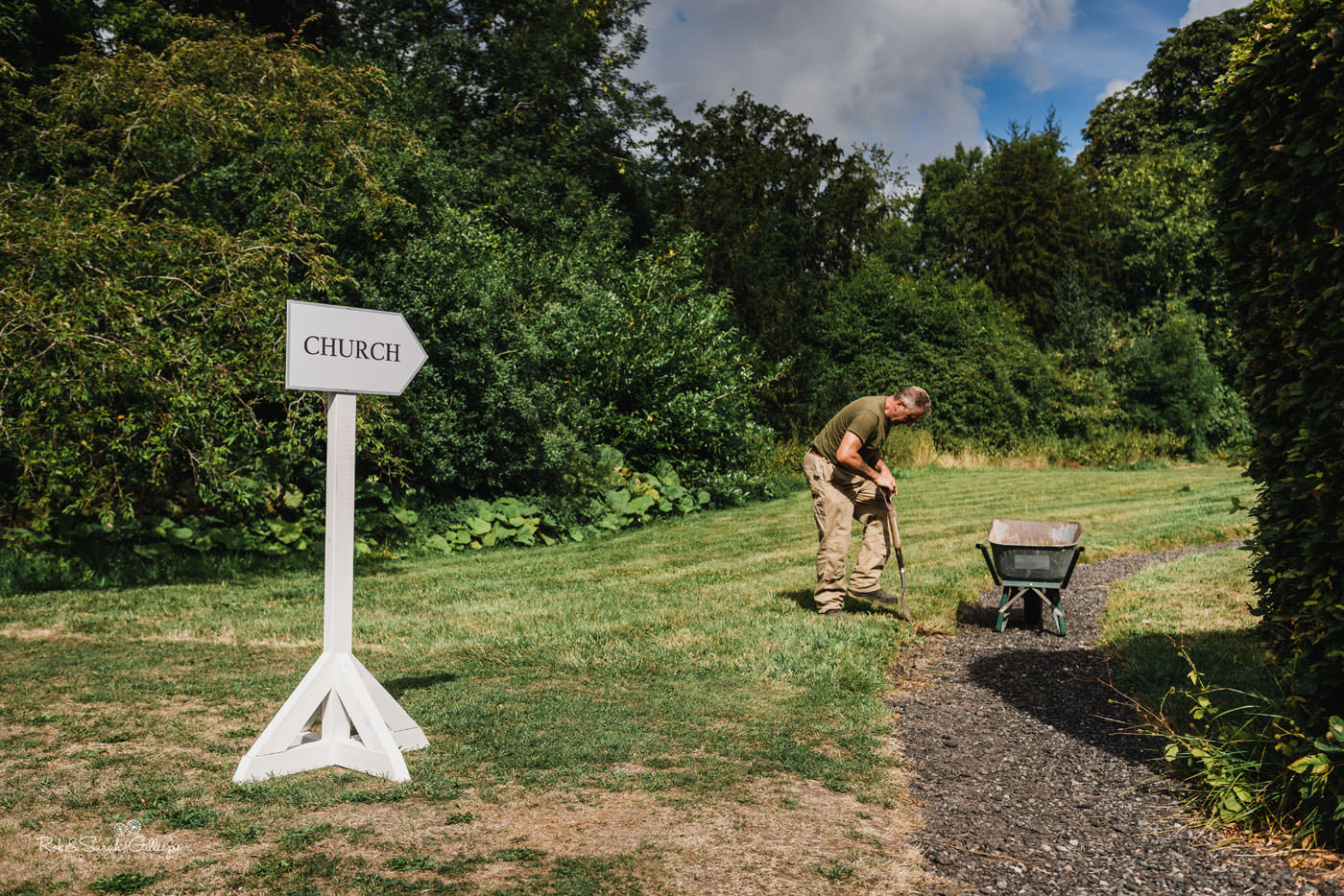 Sign pointing to church at Delbury Hall as gardener works in background