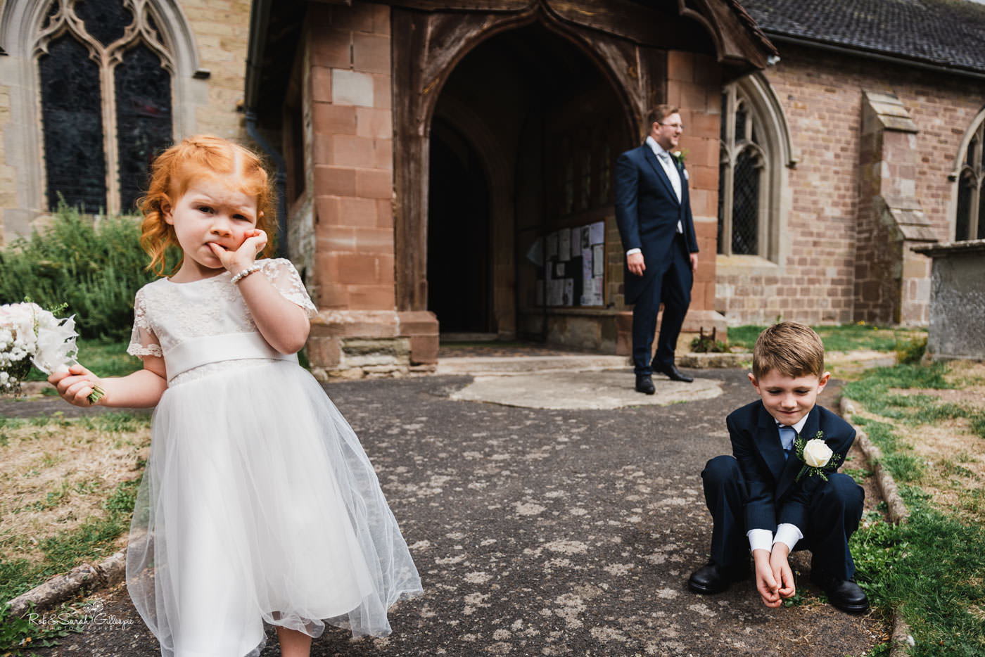 Flower girl and pageboy wait for wedding at St Peter's Church Diddlebury