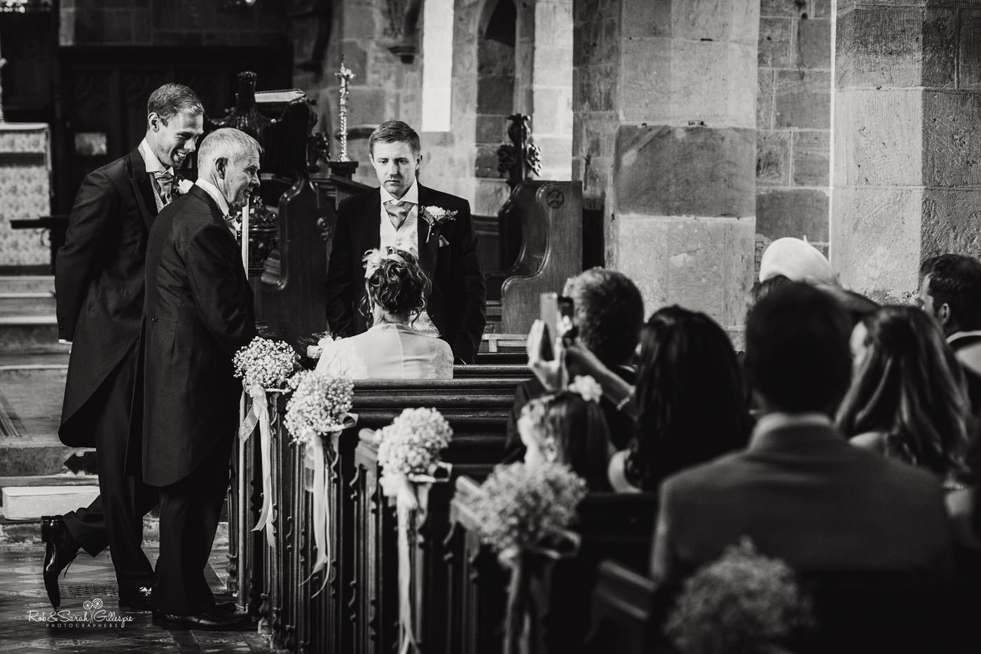 Groom and friends wait for bride at St Peter's Church in Diddlebury