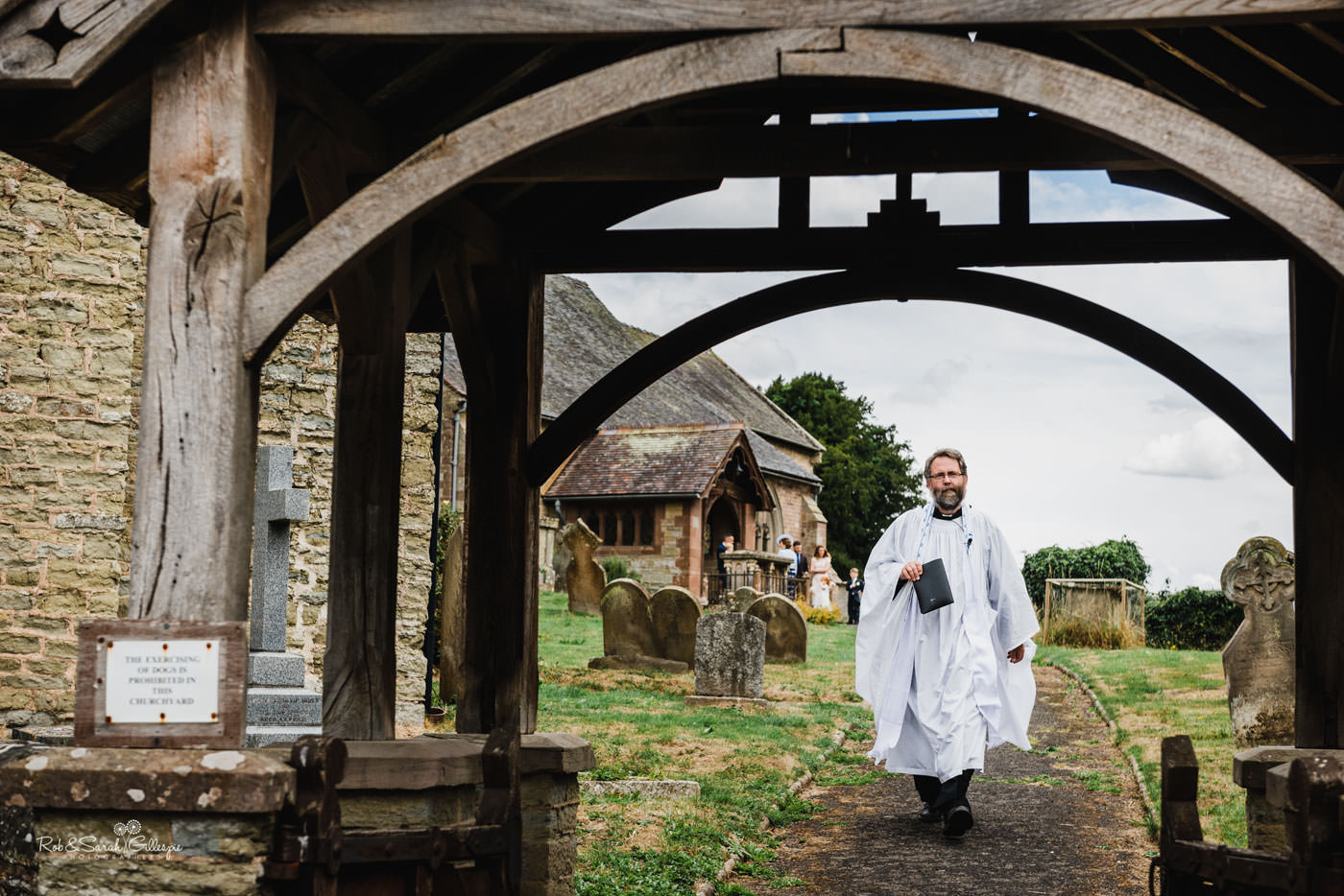 Vicar at St Peter's Church Diddlebury greets bride as she arrives for wedding