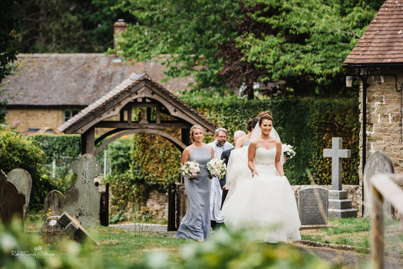 Bride and bridesmaids walk towards St Peter's Church in Diddlebury, Shropshire