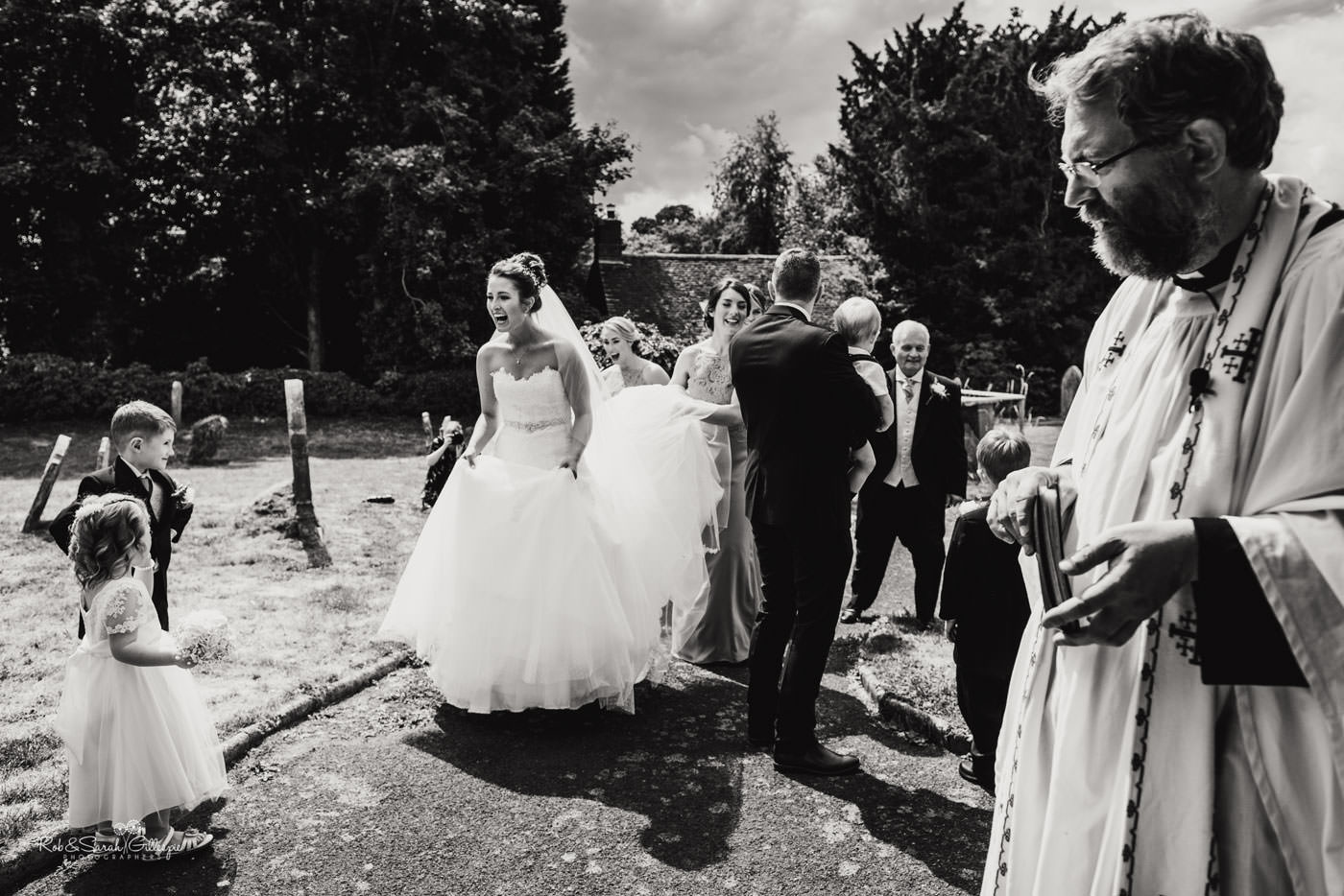 Bride greets wedding guests at St Peter's Church Diddlebury