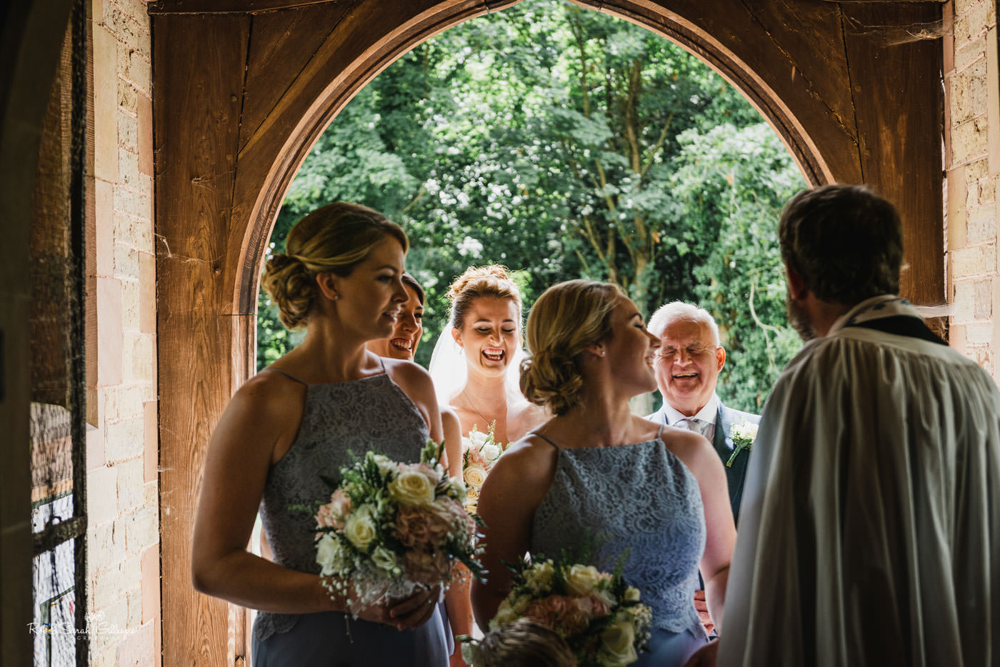 Bride and bridesmaids in church doorway at St Peter's Diddlebury