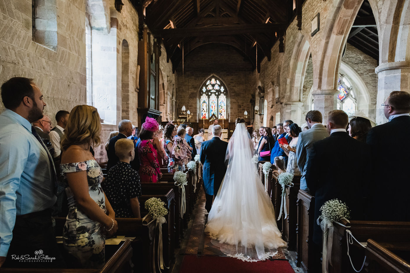 Bride and dad enter wedding ceremony at St Peter's Church Diddlebury