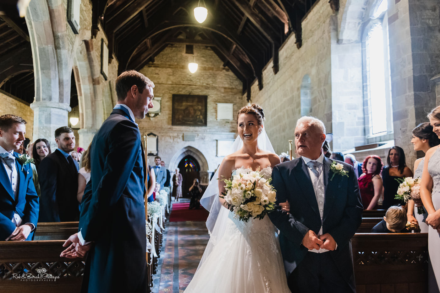 Bride and dad enter wedding ceremony as groom watches