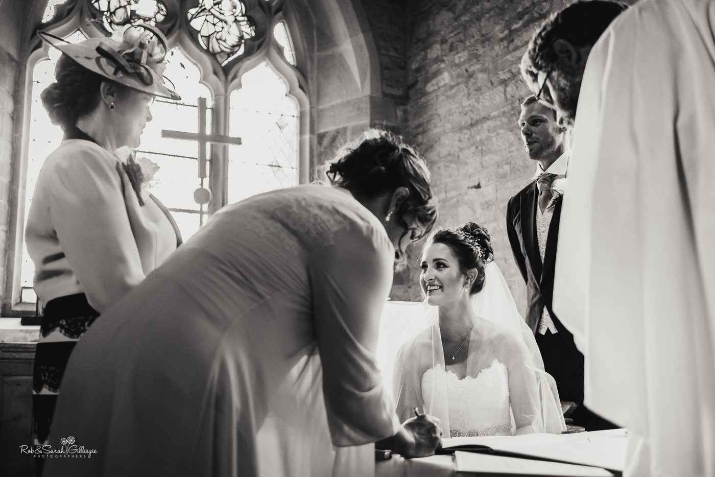Bride signs wedding register at St Peter's Church Diddlebury