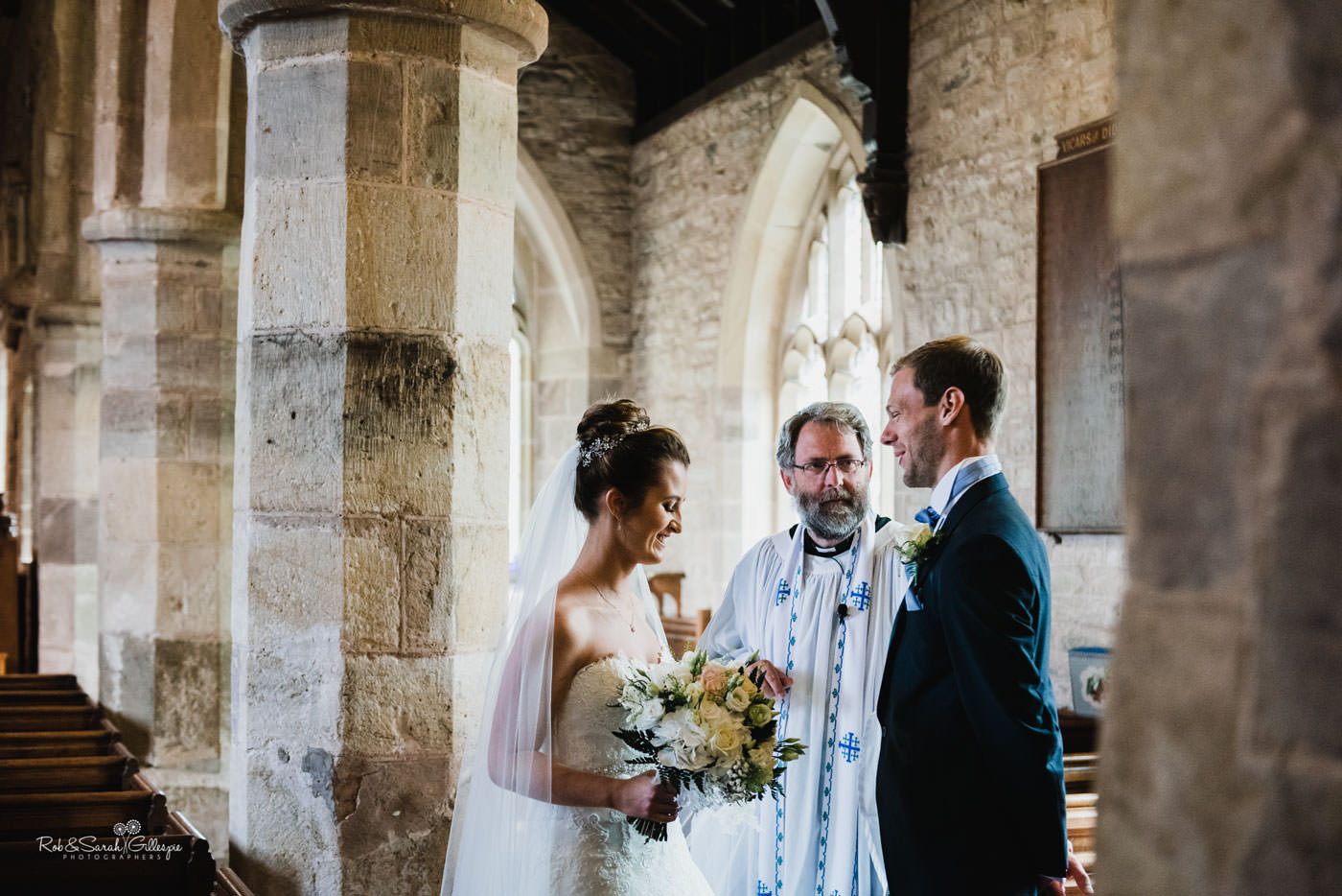 Bride and groom walk down aisle at St Peter's Church Diddlebury
