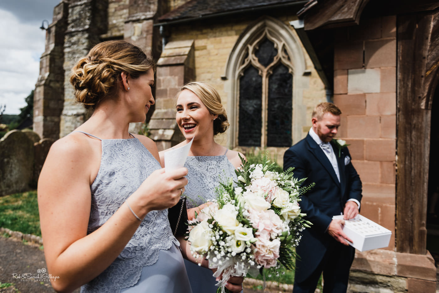 Bridesmaids chat as they wait for bride and groom to leave church