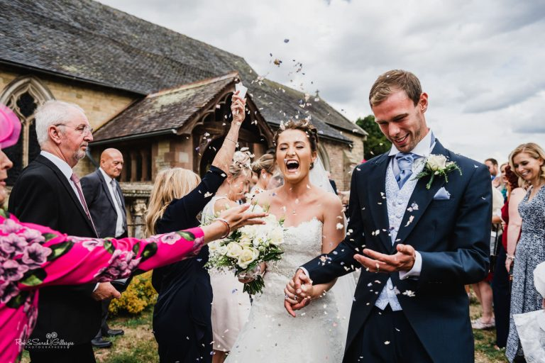 Bride and groom with confetti at Delbury Hall in Shropshire