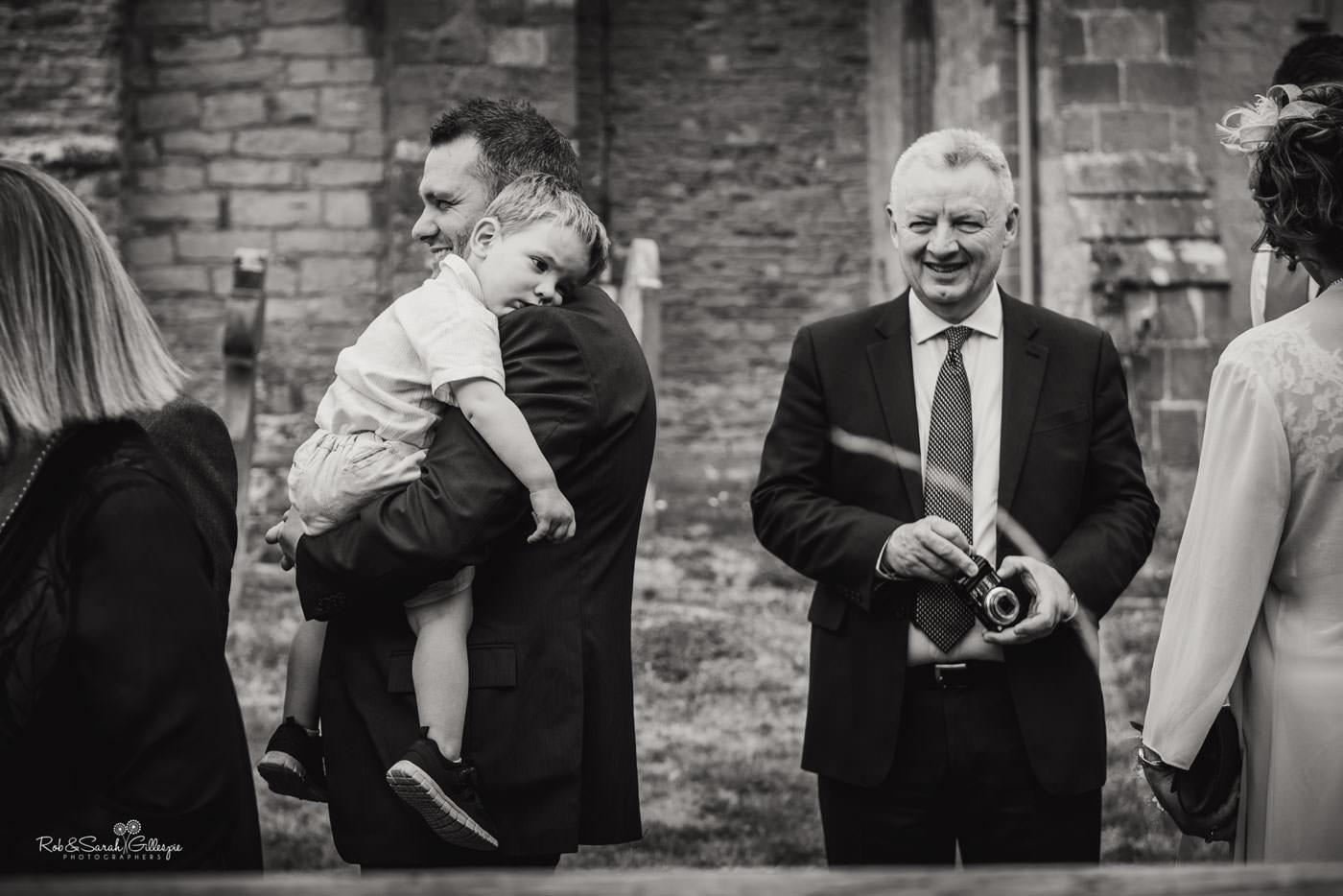 Wedding guests congratulate bride and groom at St Peter's Church Diddlebury in Shropshire