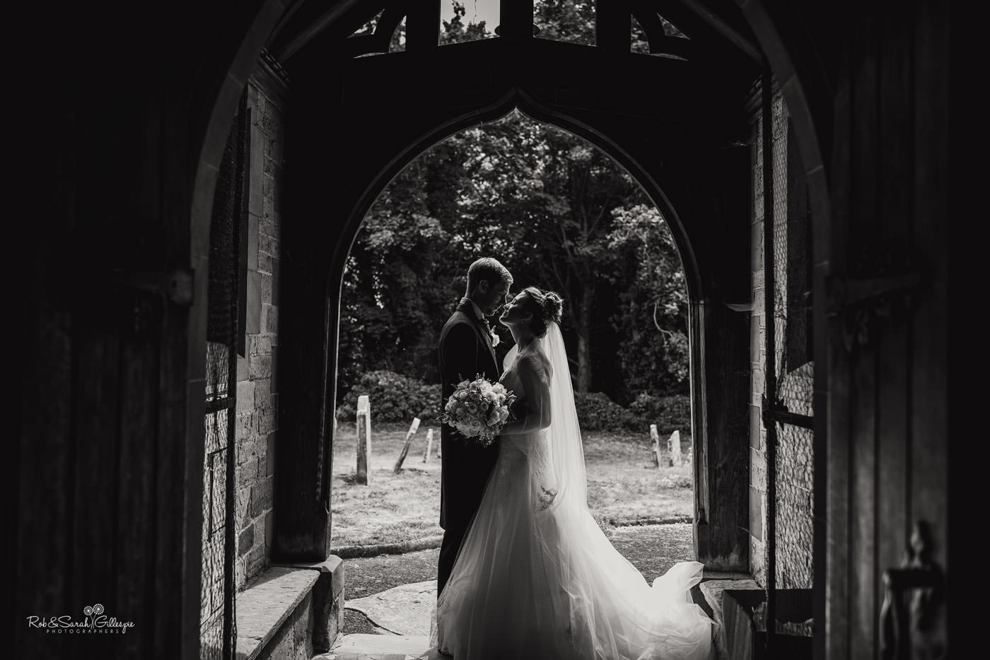 Bride and groom in doorway at St Peter's Church in Diddlebury