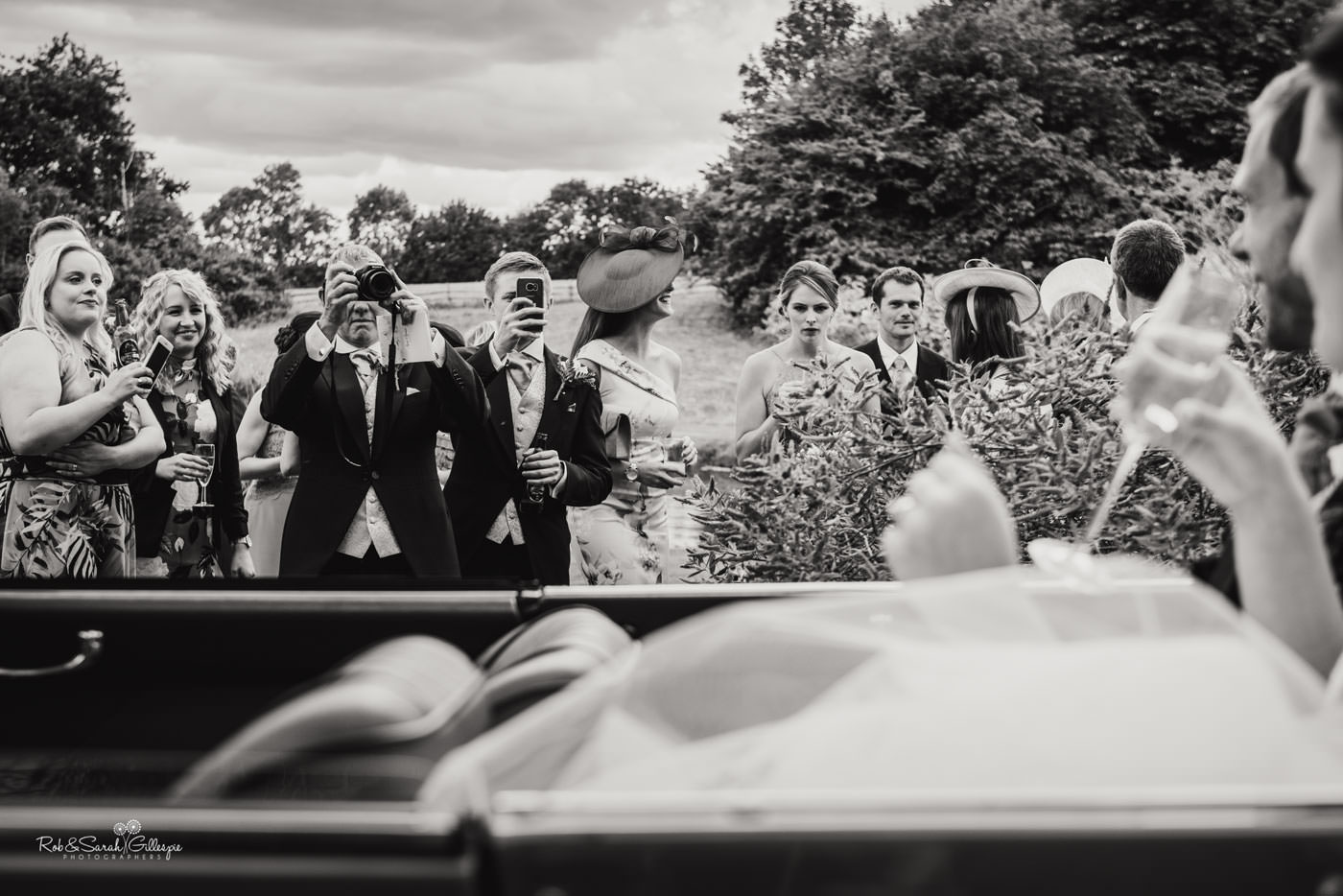 Wedding guests take photos of bride and groom at Delbury Hall