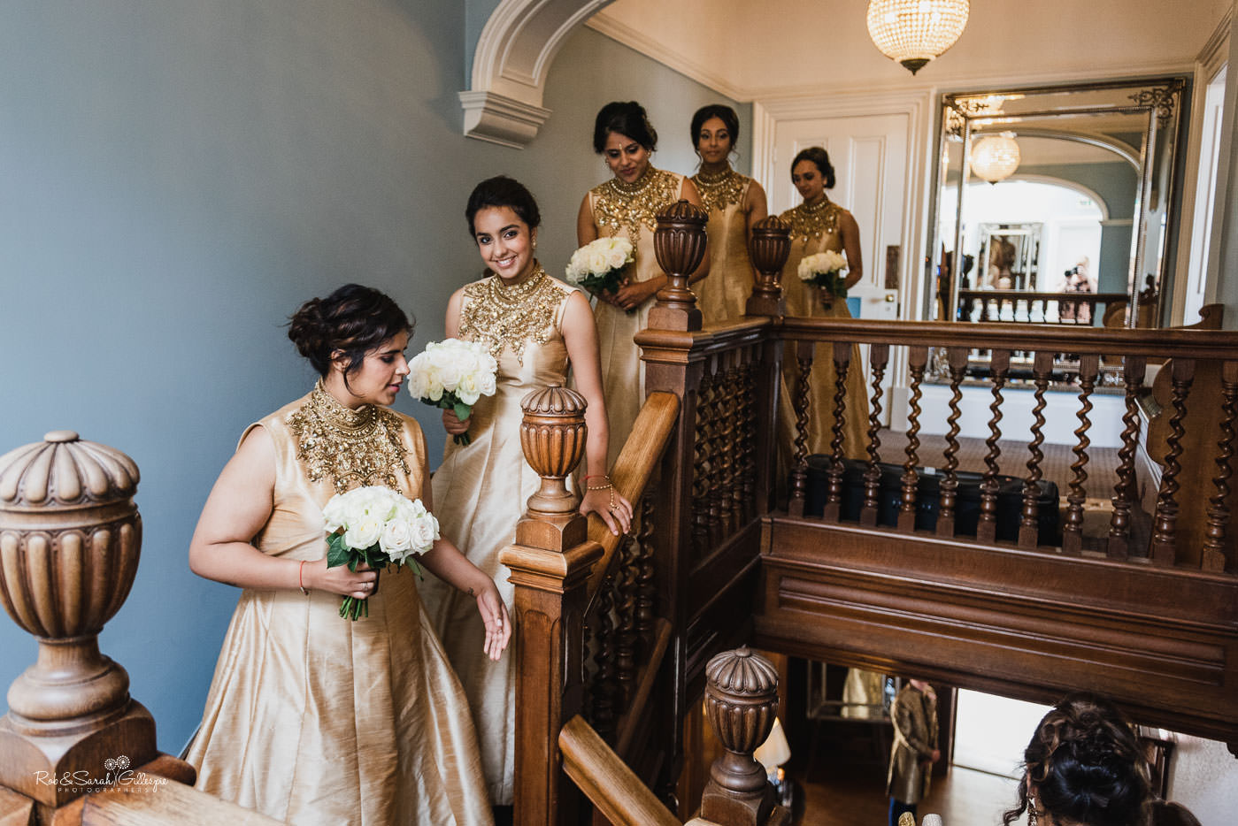 Bridesmaids on staircase at Pendrell Hall in traditional Indian outfits