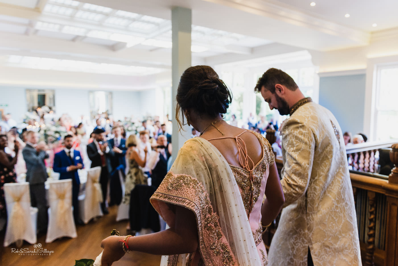 Bride and groom enter wedding breakfast at Pendrell Hall fusion wedding