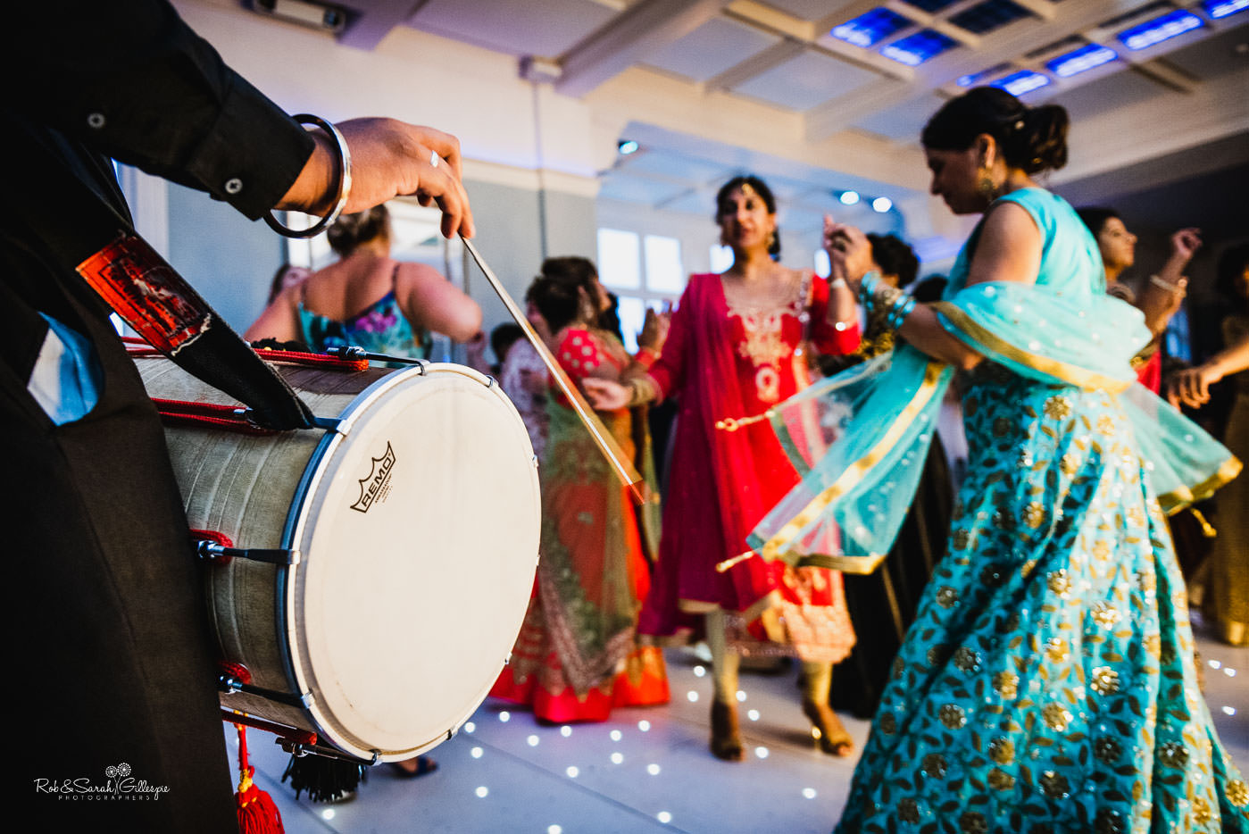 Bride and guests dancing with dhol drums at Pendrell Hall fusion wedding