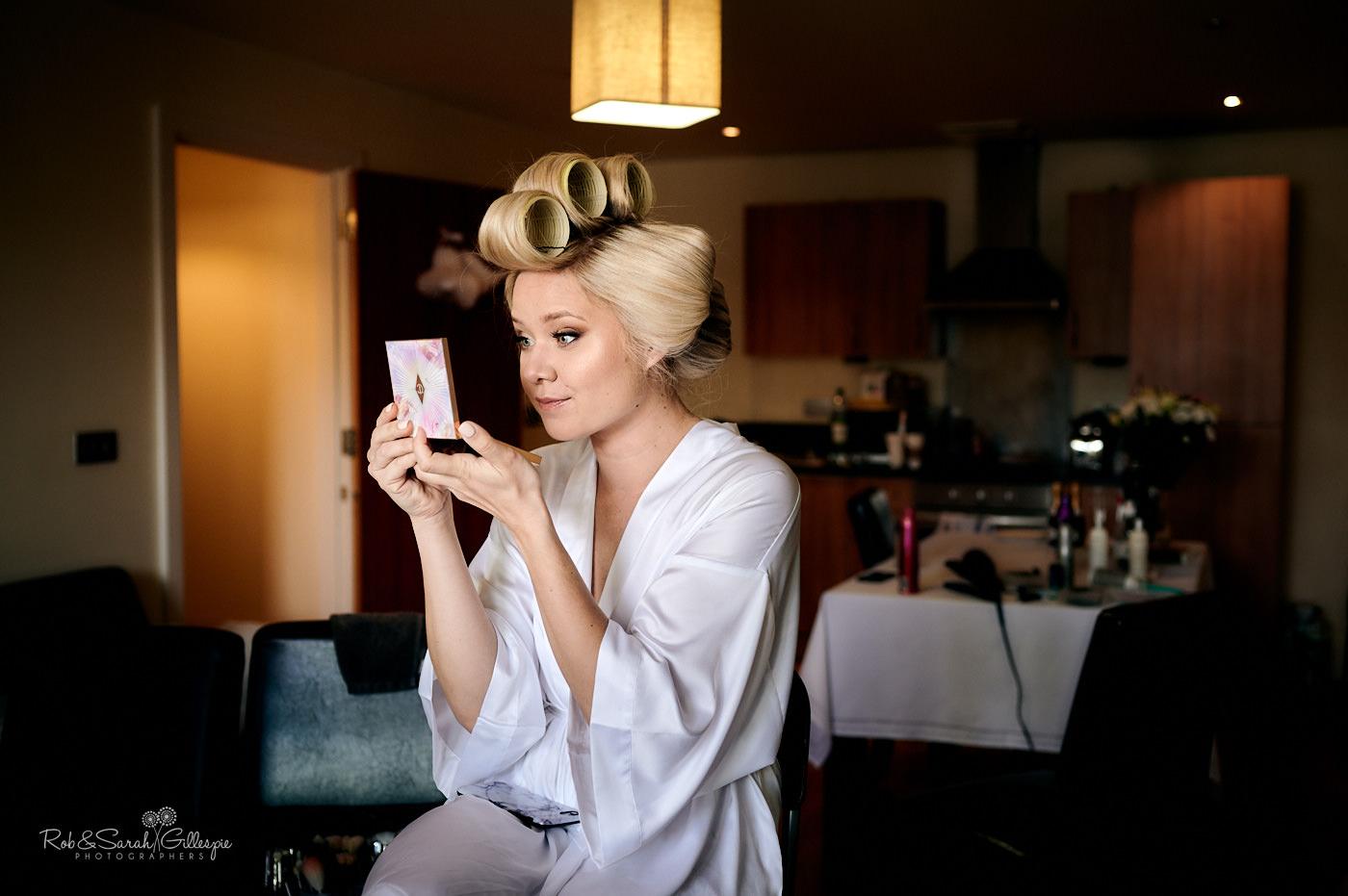 Bride checks makeup in mirror
