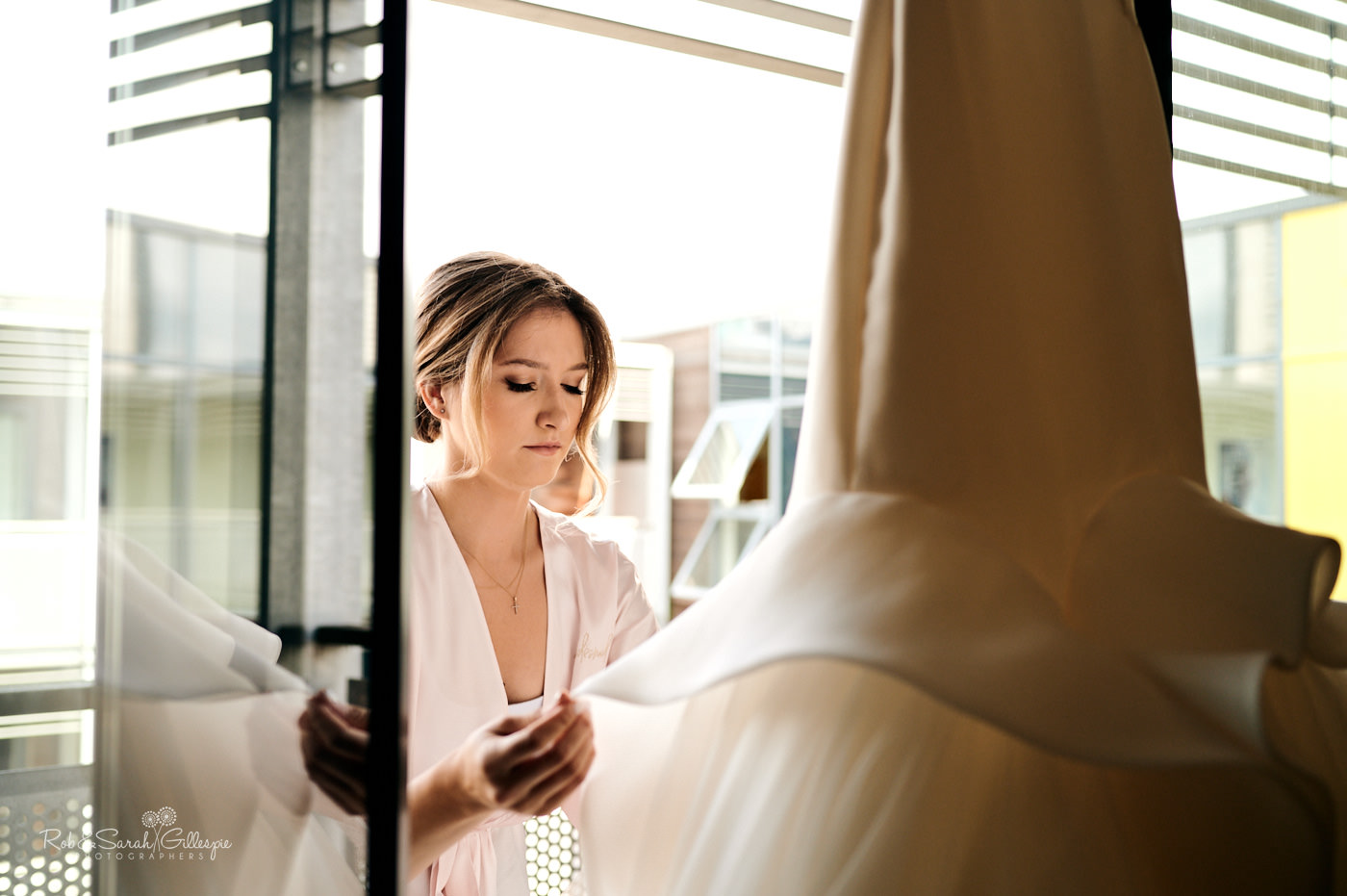 Bridesmaid adjusts wedding dress in window