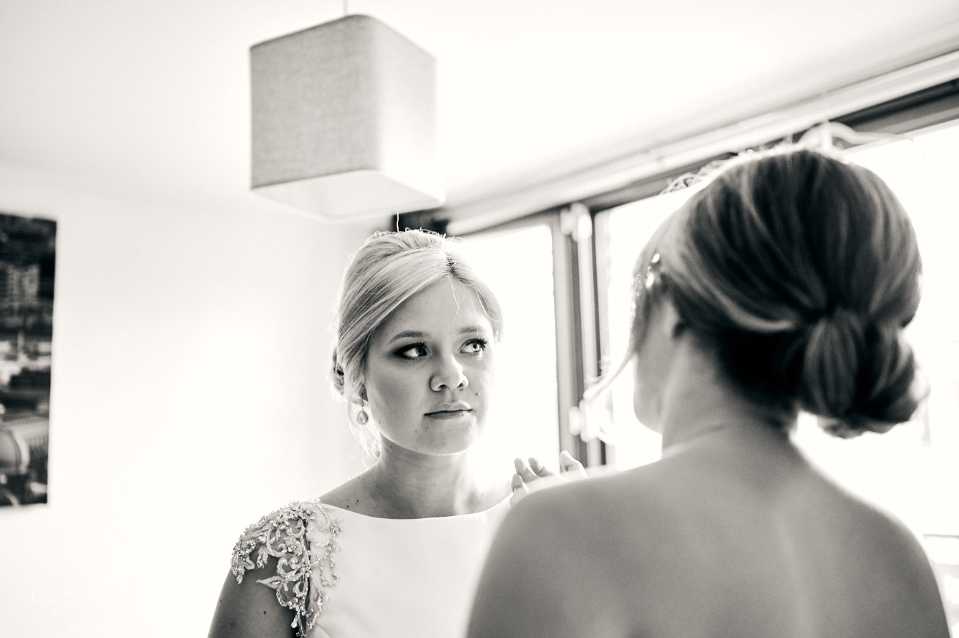Bride and bridesmaid chat while preparing for wedding