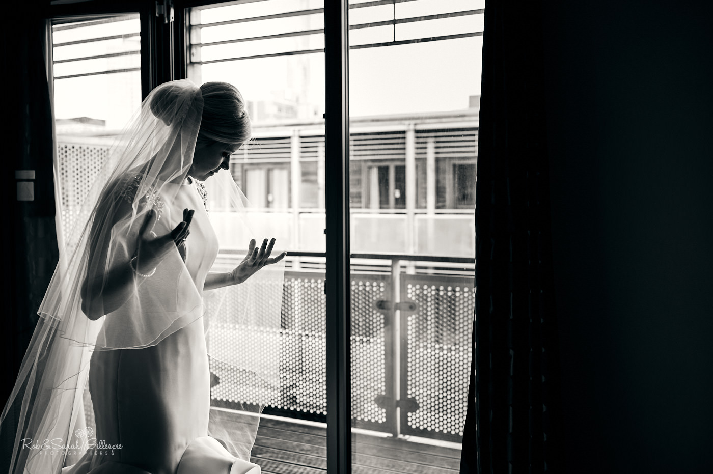 Bride adjusts her veil in window light