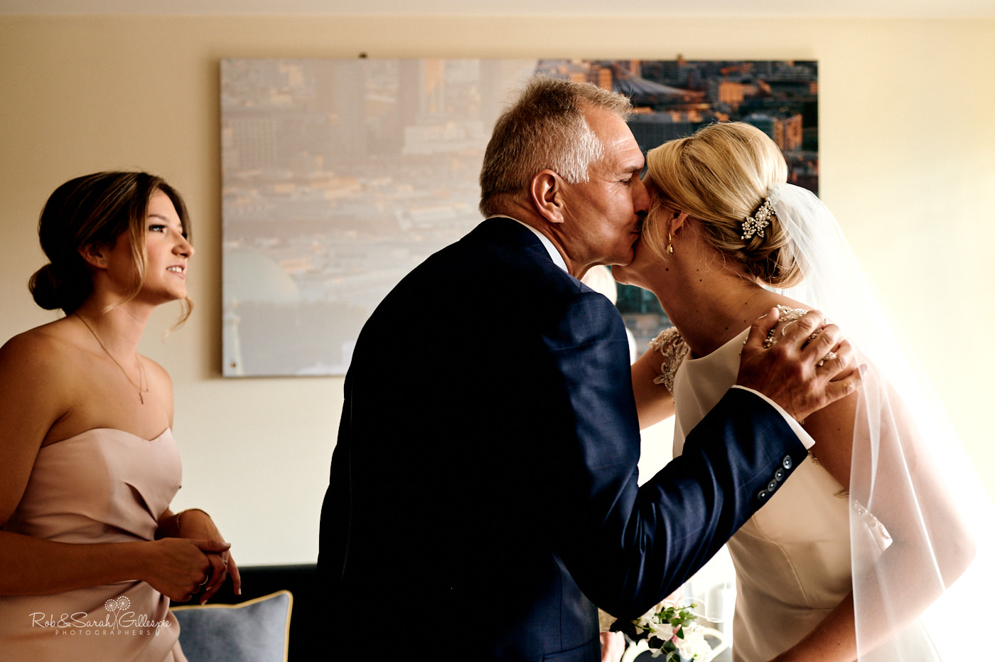 Bride's father kisses his daughter while preparing for wedding
