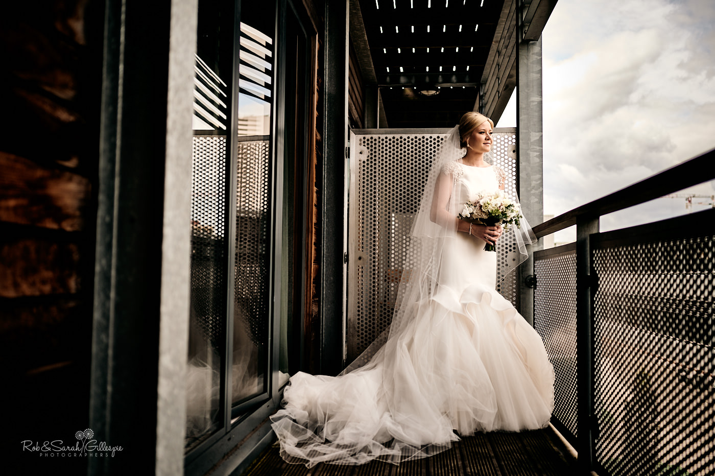 Bride portrait on balcony holding bouquet