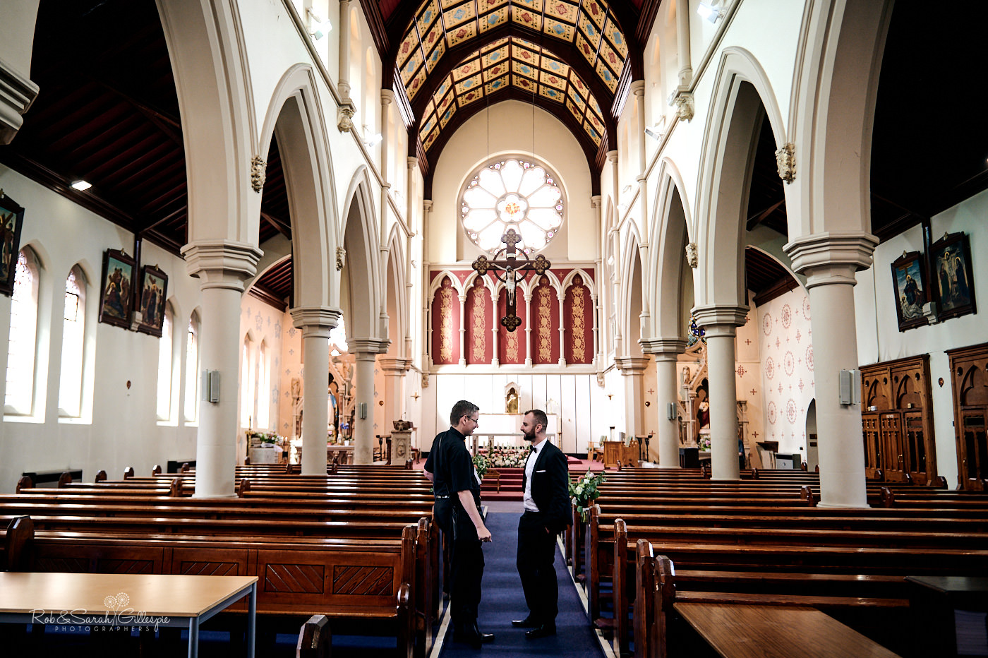 Groom greets wedding guests inside St Anne's Roman Catholic church in Digbeth, Birmingham